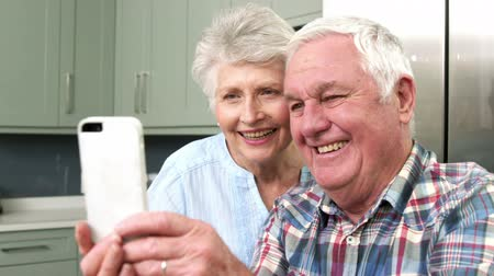 elliler : Smiiling old couple taking a selfie with a smartphone