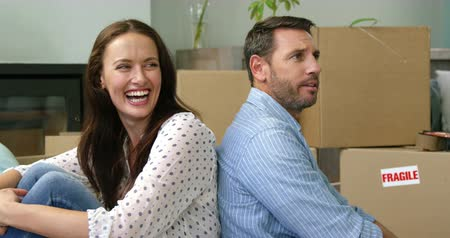 home life : A couple back to back moving in a new place laughing