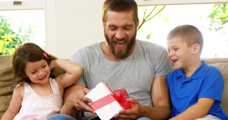 surprised : Children offering a gift to their father on a couch Stock Footage