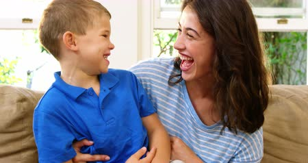 oğlum : Mom and son laughing in the living room on a couch