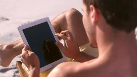 abandonment : A man is using a multimedia object on the beach Stock Footage