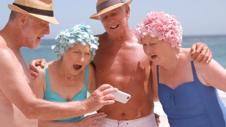 companionship : A group of mature friends are watching a smartphone on the beach