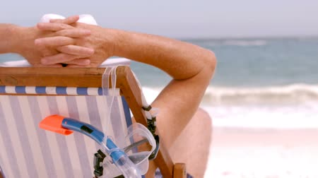abandonment : A mature man is sitting on a deck chair on a beach Stock Footage