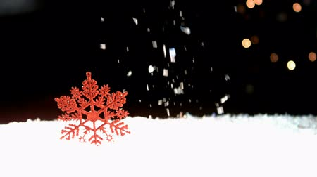 feliz natal : Snowing on a red snowflake against a black background
