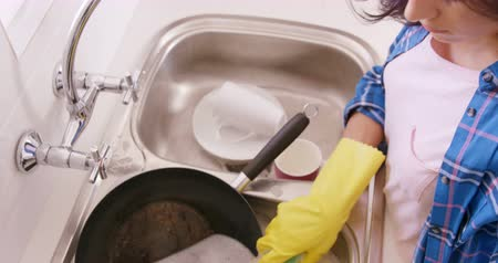 dish : Woman washing the dishes in the kitchen