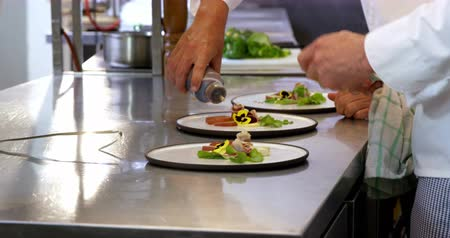 сотрудники : Chefs preparing plates in the kitchen