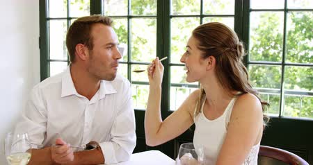 nóbl : Couple feeding each other and smiling while spending time at the restaurant