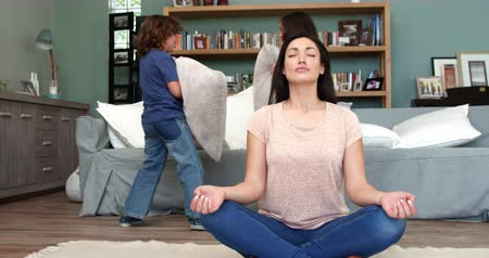 stress : A mother trying to relax while her children are fighting in the lounge Stock Footage
