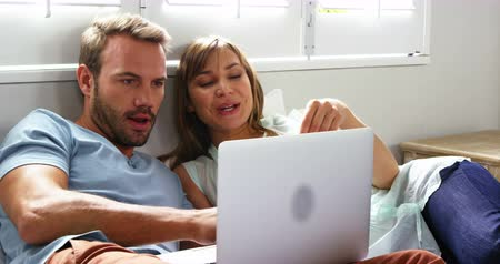 website : Happy couple lying on bed going shopping by internet at home