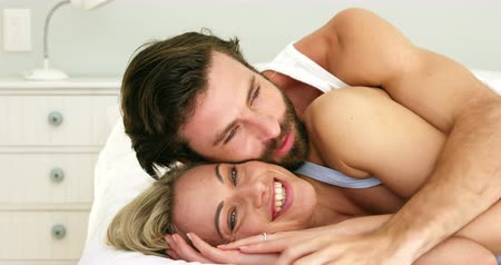 párosít : Cute couple lying on a bed embracing each other at home