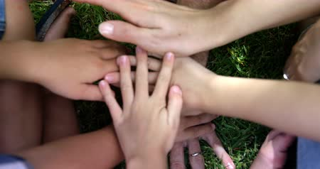 kézi : Happy family putting their hands as a team in the garden