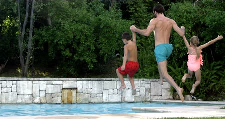otec : Father jumping with his children in the pool