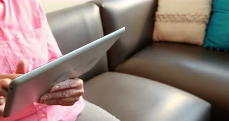 společenská místnost : Close up view of retired woman playing with tablet computer in retired home