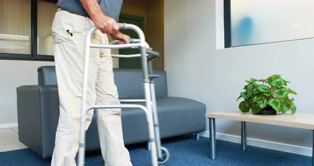 sufferance : Patient helping himself to have a sit thanks to his zimmer frame in a medical office