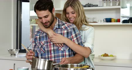 megölel : Cute girl hugging his boyfriend while he is cooking food in the kitchen