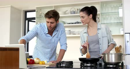 culinária : Cute couple learning how to cook by watching a tutorial on internet