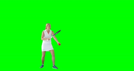 tennis whites : Side view of sportswoman is practising tennis against a green screen