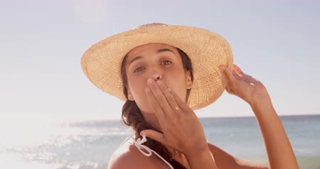 üfleme : Happy woman blowing a kiss on a beach