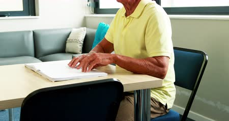 persiana : Blind senior man reading a book in retired home Stock Footage