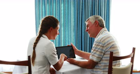 helping : Nurse and senior man using tablet in medical office
