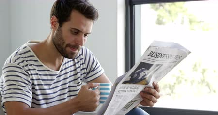 ler : Man is reading newspaper at home