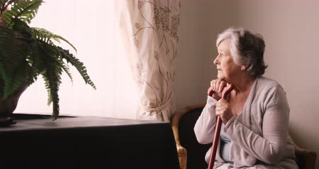 confuso : Thoughtful senior woman looking through window at home