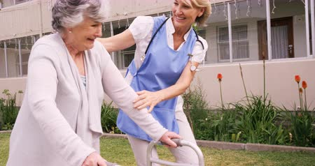 caregiver : Female nurse assisting a senior woman to walk in garden