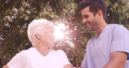 caregiver : Male nurse assisting a senior woman to walk in the backyard of hospital