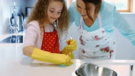kötény : Mother assisting daughter in cleaning kitchen at home