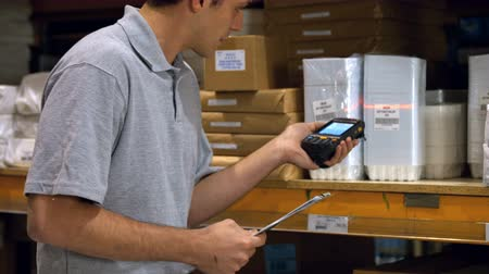 inventário : Worker holding checklist and scanning products with a barcode scanner in warehouse