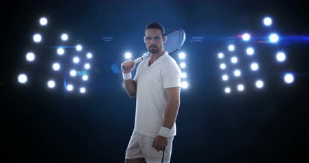 atleta : Portrait of young man standing with the racket in front of the floodlight 4k Stock Footage
