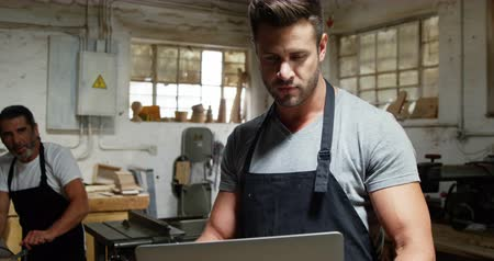 workshop : Two carpenters looking at laptop while working in workshop Stock Footage
