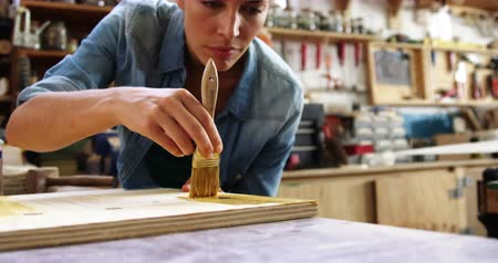 marangoz : Focus on carpenter painting a wooden plank in workshop