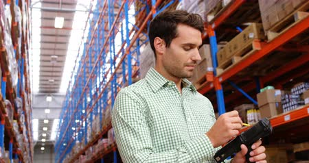 inventário : Warehouse worker doing inventory in a warehouse Vídeos
