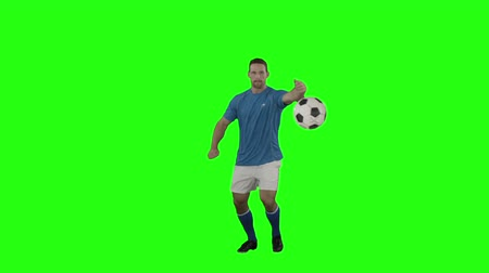 jogador : Soccer player striking a ball on a green screen Vídeos