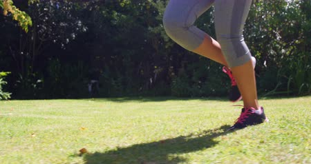 nogi : Close up of sportswoman running in a park Wideo