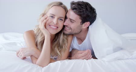 sheet : Cute couple smiling while being under bed sheet in bedroom Stock Footage