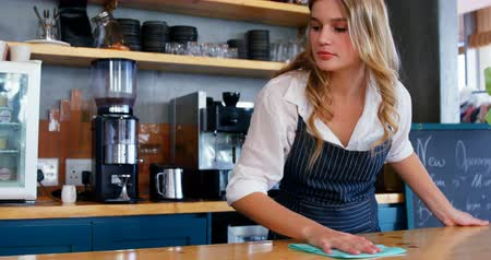 counter : Young waitress is cleaning the counter at restaurant