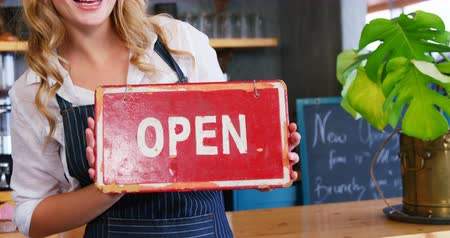 garçonete : Portrait of happy waitress is holding open sign at restaurant