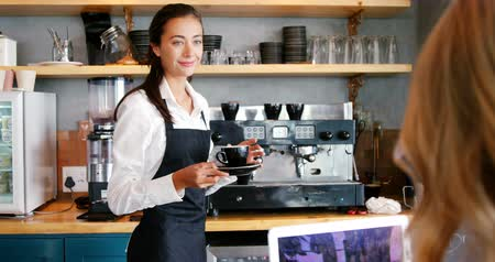 porce : Waitress serving a cup of coffee to a woman in restaurant 4k