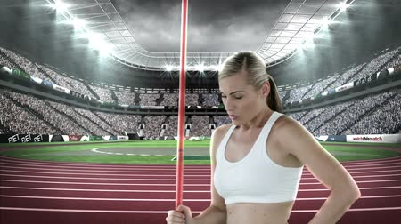 javelin : Female athlete standing with javelin throw in a stadium at night