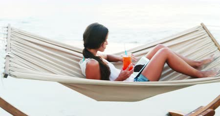гамак : Woman relaxing on hammock and using digital tablet at beach 4k Стоковые видеозаписи
