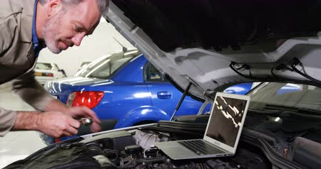 garagem : Mechanic using laptop while servicing a car engine at repair shop 4k Vídeos