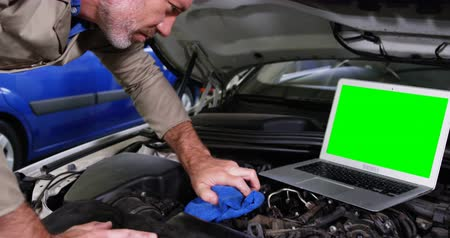 szerelő : Mechanic using laptop while servicing a car engine at repair shop 4k Stock mozgókép