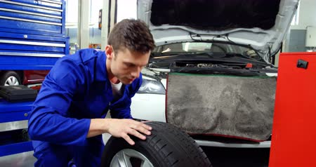 pneus : Mechanic checking tyre and making ok sign in repair shop 4k