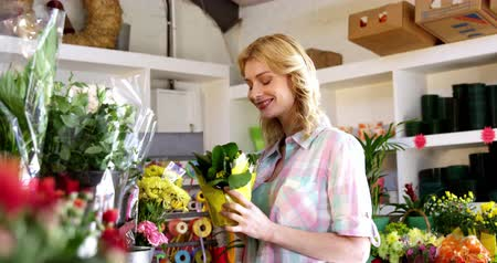 florista : Slow motion of beautiful female florist smelling flower in flower shop