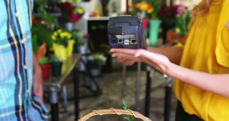 payment : Costumer making payment through credit card in flower shop Stock Footage