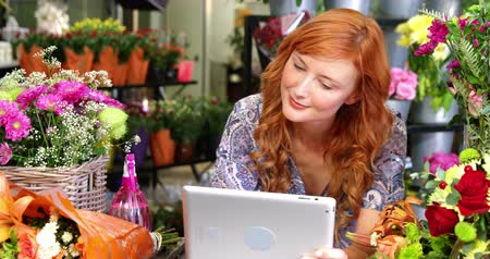 kwiaciarnia : Happy female florist using digital tablet in florist shop