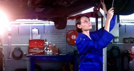garagem : Female mechanic servicing a car in garage 4k