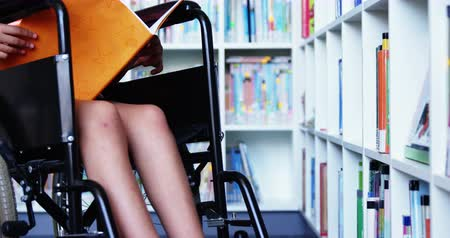 fogyatékosság : Slow motion of disabled school girl reading book in library at school 4k Stock mozgókép